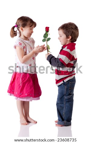 Cute little boy giving a rose to a girl - stock photo