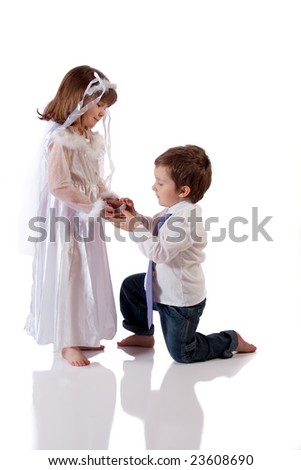 Cute little boy giving an engagement ring to a girl