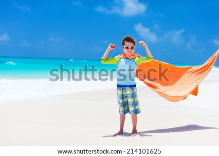 Cute little boy having fun on tropical beach during summer vacation - stock photo