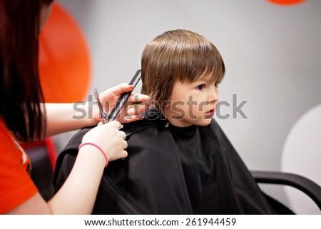Cute little boy, having haircut in barber shop - stock photo