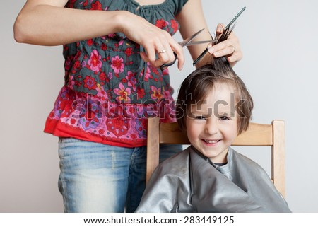 Cute little boy, having haircut, smiling happily, white background - stock photo