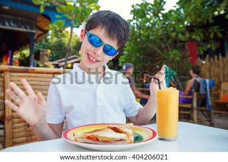 Cute little boy having lunch in outdoors restaurant - stock photo
