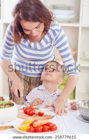 Cute little boy helping his mother in the kitchen with food preparation - stock photo