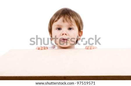 Cute little boy hidden behind a table. Isolated on white. - stock photo