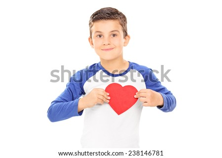 Cute little boy holding a heart shaped cardboard on his chest isolated on white background - stock photo