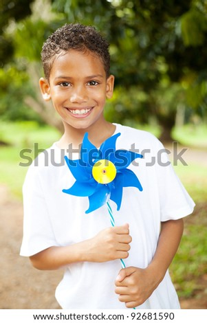 cute little boy holding a pinwheel outdoors - stock photo