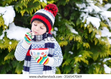 Cute little boy holding big cup with snowflakes and hot cocoa and chocolate drink and marshmallows. Kid boy in winter sweater, hat, long warm scarf and colorful gloves. On cold snowy winter day. - stock photo