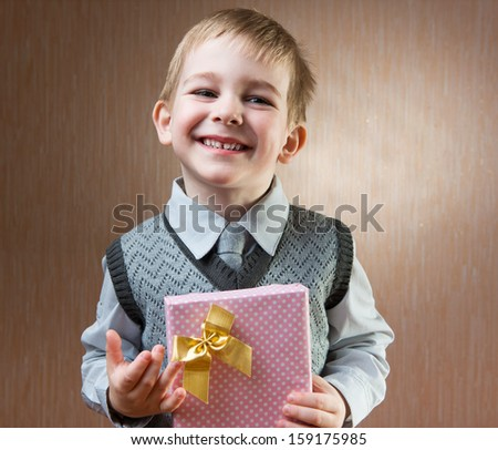 Cute little boy holding gift box with bow - stock photo