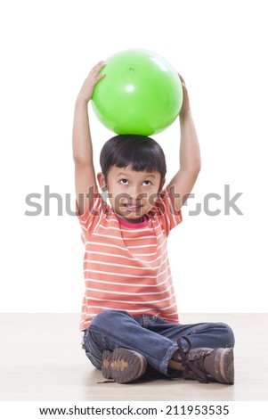 Cute little boy holding head over to the green ball  - stock photo