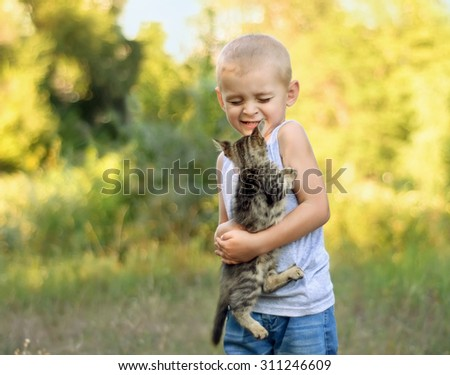 Cute little boy holding kitten in a park - stock photo