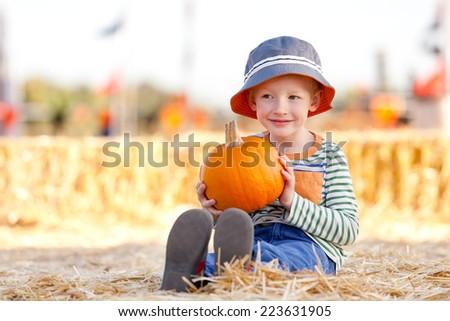 cute little boy holding pumpkin at pumpkin patch - stock photo
