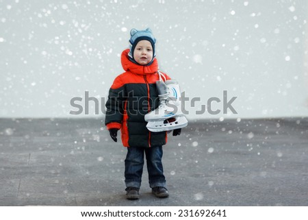 cute little boy  holds the skates wearing warm winter clothes  going ice skating, snow - stock photo
