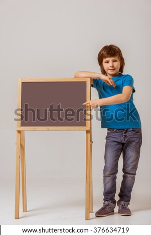 Cute little boy in a blue t-shirt leaning on a blackboard and pointing on it, looking in camera and smiling while standing on a gray background - stock photo
