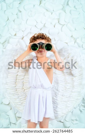 Cute little boy in a costume of angel looking through the binoculars. Cupid. Valentine's day. - stock photo