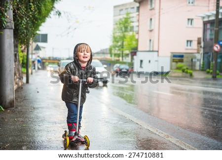 Cute little boy in a very wet clothes on the scooter next to road under the rain - stock photo
