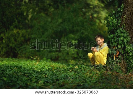 cute little boy in a yellow shirt and jeans sitting on a tree ivy - stock photo