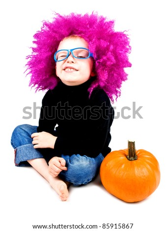 Cute little boy in big pink wig with halloween pumpkin making funny face on white background - stock photo