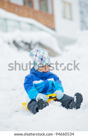 Cute little boy in blue riding on a sled near  the Austrian cottage - stock photo