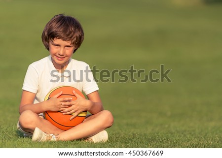 Cute little boy in casual clothes is holding a ball, looking at camera and smiling while sitting on the grass in the park - stock photo