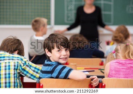 Cute little boy in class at school turning back on his chair to look at the camera with a friendly smile
