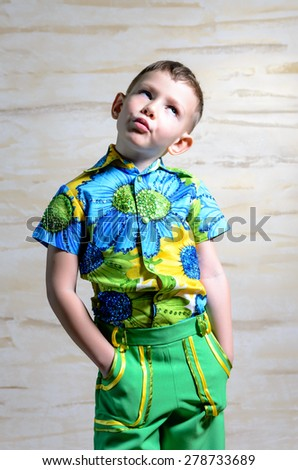 Cute little boy in colorful clothes standing thinking staring up into the air with a contemplative expression and his hands in his pockets - stock photo