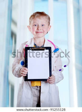 Cute little boy in doctor uniform with clip board in hands on light blue hospital background - stock photo