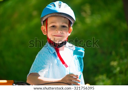 Cute little boy in helmet on bike in forest - stock photo