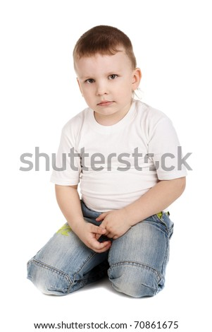 cute little boy in jeans sitting on the floor