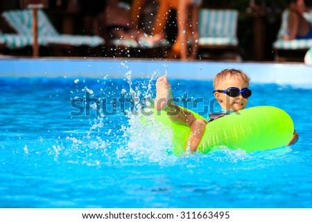 cute little boy in life ring having fun in the swimming pool - stock photo