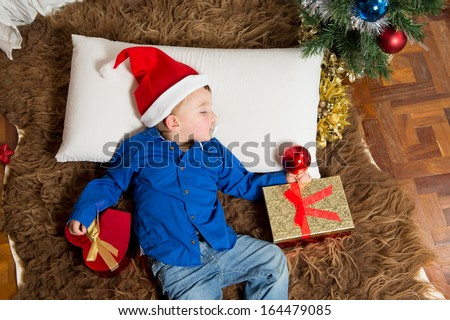 Cute Little boy in Santa Claus hat sleeping on Rug at Christmas - stock photo
