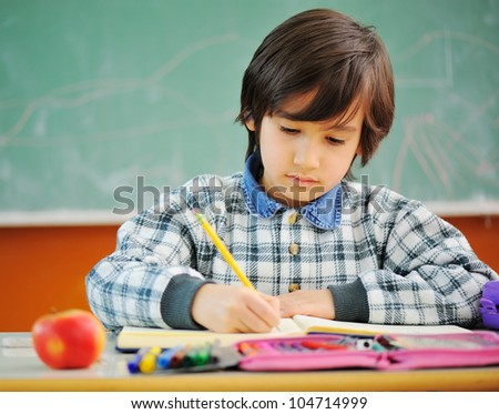 Cute little boy in school in front of blackboard - stock photo