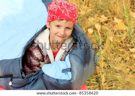 Cute little boy in sleeping bag outdoor. - stock photo