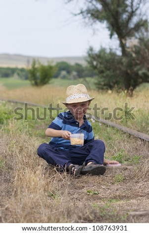 Cute little boy in summer hat sitting on railway and eating lunch - stock photo