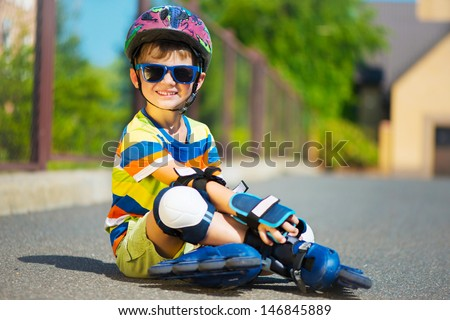 Cute little boy in sunglasses and helmet with rollers - stock photo
