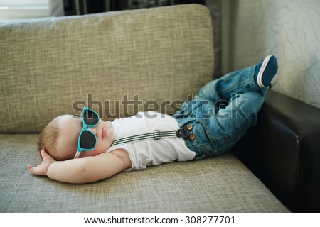 cute little boy in sunglasses at home - stock photo