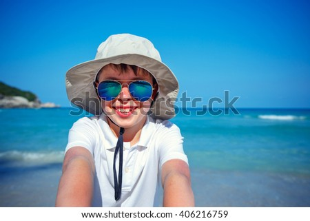 Cute little boy in sunglasses making selfie at tropical beach on exotic island during summer vacation - stock photo