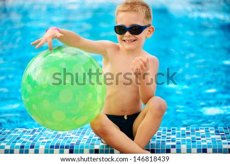 Cute little boy in sunglasses sitting at swimming pool - stock photo