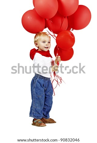 cute little boy in white shirt, jeans and red scarf smiling as he holds a bunch of red balloons - stock photo