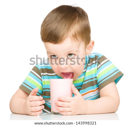 Cute little boy is dipping his tongue in the glass of milk, isolated over white - stock photo