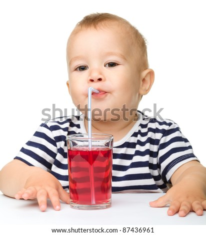 Cute little boy is drinking red juice using straw while sitting at table, isolated over white - stock photo