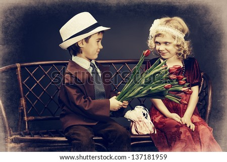 Cute little boy is giving bouquet of tulips to the charming little lady. Retro style. - stock photo