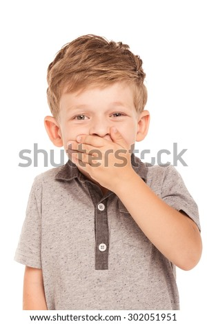 Cute little boy is isolated on white background. Boy looking at camera, cheerfully laughing and covering his mouth with hand - stock photo