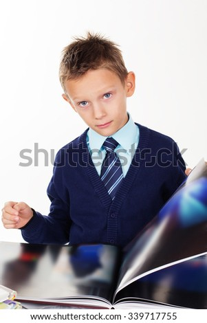 Cute little boy is looking at pictures in a book, isolated over white background
