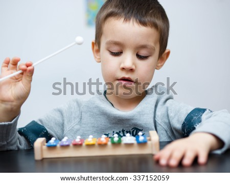 Cute little boy is playing a musical instrument - stock photo
