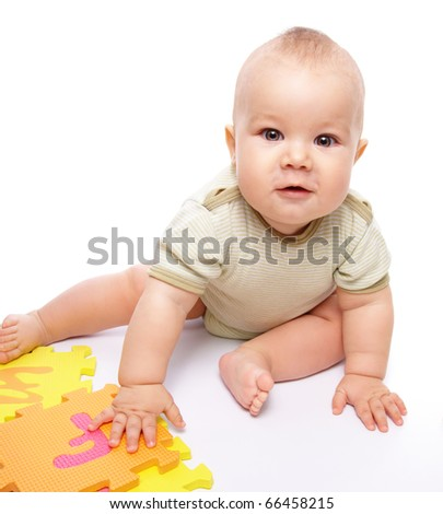 Cute little boy is playing with alphabet while sitting on floor, isolated over white
