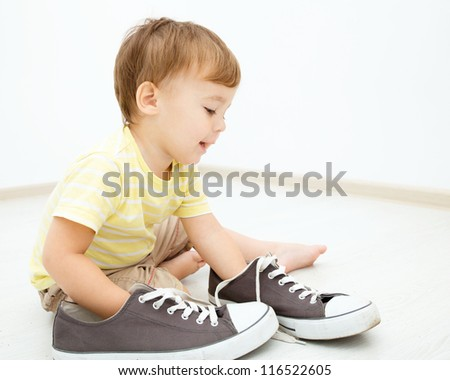 Cute little boy is playing with big sneakers while sitting on the floor - stock photo