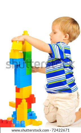 Cute little boy is playing with building blocks - stock photo