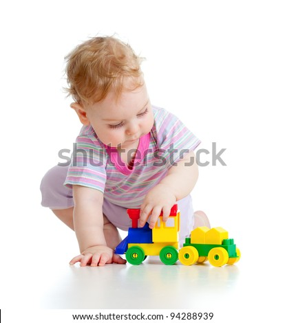 Cute little boy is playing with colorful train isolated on white - stock photo