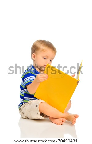 Cute little boy is reading a book