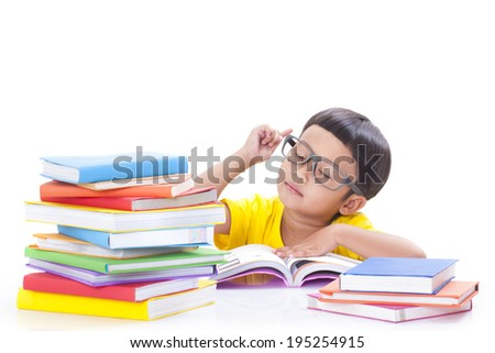 Cute little boy is reading a book while wearing glasses.